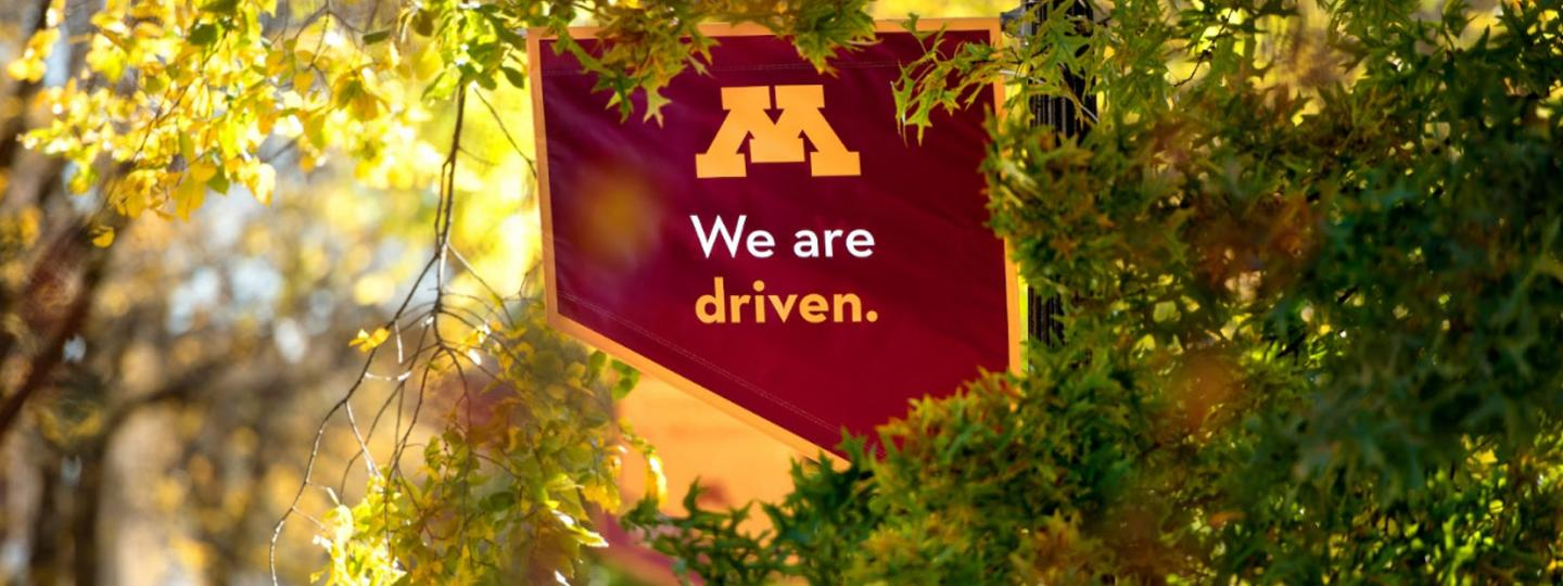 "UMN Campus Mall Banner: ""We Are Driven"""