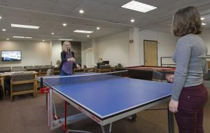 Students playing ping pong in the gaming area of the main lounge.