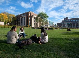 Small group of students sit together on East Bank mall lawn.