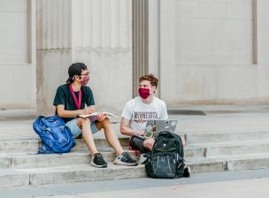 Students wearing face coverings study outside