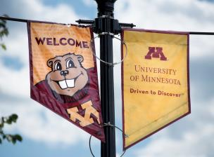 U of M flagpole signs depicting Goldy Gopher and the university logo.