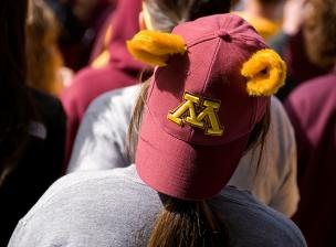 A person wearing a backward U of M hat with gopher ears on top